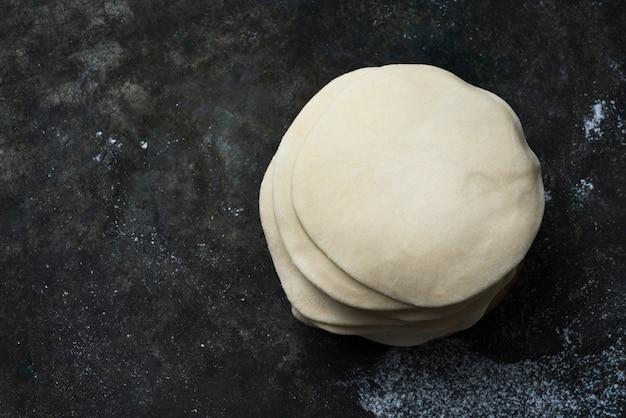 Walcowane niegotowane ciasto na indyjskie chapati na podpłomyki. gotowy do gotowania koncepcja. łatwe posiłki. domowe gotowanie. widok z góry flat lay