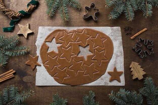 Walcowane niegotowane ciasto z rzeźbionymi kształtami gwiazdek na świąteczne przysmaki na stole kuchennym ozdobione wiecznie zielonymi gałązkami