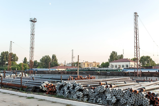 Walcowanie metali, rury składane w magazynie kolejowym przygotowywane są do wysyłki,
