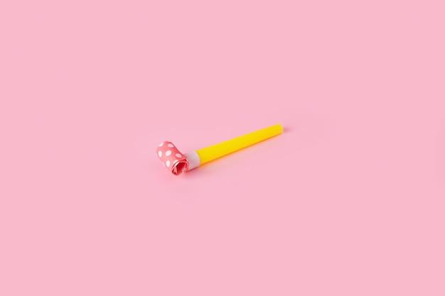 Walcowany róg gwizdka świątecznego lub imprezowego na różowym tle
