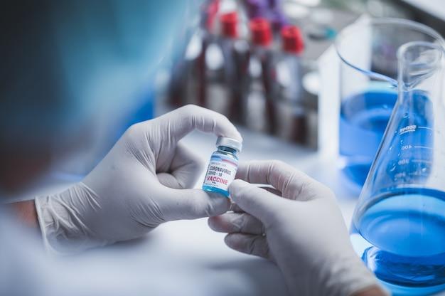 Walcz z covid-19, badaniami szczepionki przeciwko koronawirusowi w szpitalnym laboratorium, profesjonalni naukowcy posiadają butelkę nowej szczepionki do zastrzyku w leczeniu wirusów, lek kliniczny podczas pandemii