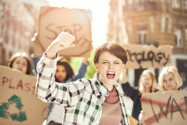 Walcząca o czystą ziemię młoda i silna kobieta protestuje na rzecz ekologii z grupą