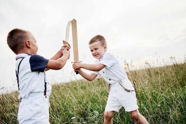 Walczmy jak prawdziwi wojownicy. dwoje dzieci, bawiąc się drewnianymi mieczami w polu.