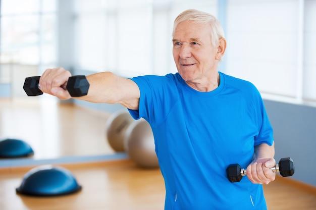 Walczy z wiekiem. pewny siebie starszy mężczyzna ćwiczący z hantlami i uśmiechający się stojąc w klubie fitness