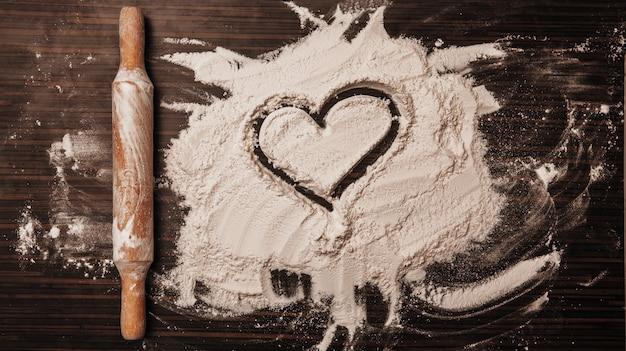 Wałek do ciasta leży obok mąki, na której widnieje symbol serca.