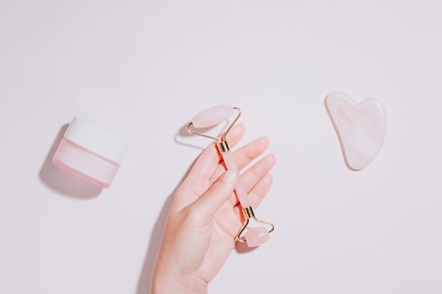 Wałek do twarzy, gua sha i krem nawilżający z zielonymi liśćmi. kosmetyki naturalne i narzędzia do twarzy na różowo. wałek kosmetyczny z różowego kwarcu, płasko leżący gua sha serca. narzędzia do pielęgnacji skóry, widok z góry