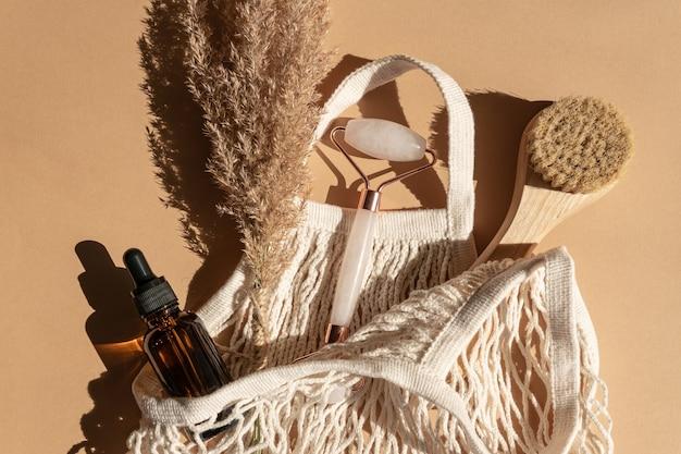 Wałek do twarzy, olejki eteryczne, pędzel do twarzy z naturalnym włosiem i pięknymi suszonymi trzcinami na beżowym tle. płaski świeckich, widok z góry. narzędzie do masażu do pielęgnacji skóry twarzy, koncepcja zabiegów kosmetycznych spa.