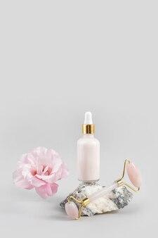 Wałek do twarzy z kwarcu kryształowego, kosmetyczna butelka z zakraplaczem na kamieniu i piękny kwiat na szarym tle. masaż twarzy do naturalnego liftingu, koncepcja piękna widok z przodu.