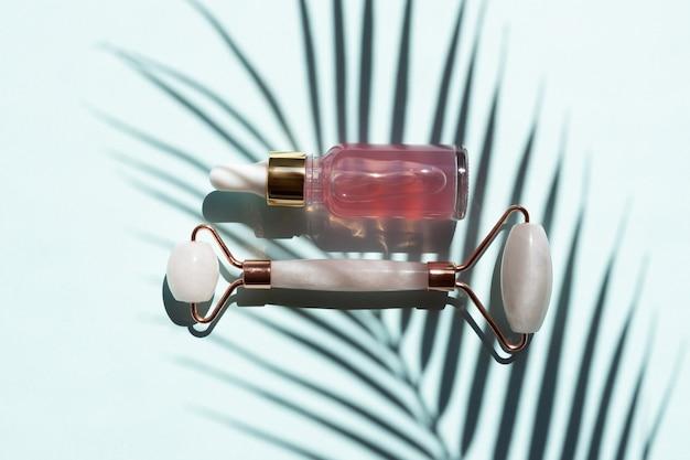 Wałek kwarcowy do masażu twarzy z różowym naturalnym zapaleniem nerek z serum kosmetycznym lub olejkiem różanym. pielęgnacyjny masaż twarzy i relaks. narzędzia do masażu domowego. zabiegi przeciwstarzeniowe i liftingujące