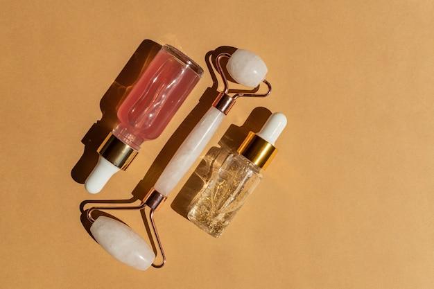 Wałek kwarcowy do masażu twarzy z różowym naturalnym zapaleniem nerek z serum kosmetycznym lub olejkiem różanym. pielęgnacyjny masaż twarzy i relaks. narzędzia do masażu domowego. zabiegi przeciwstarzeniowe i liftingujące.