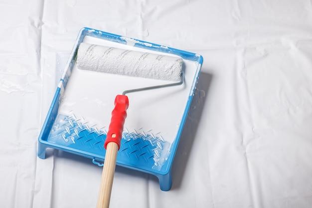 Wałek malarski na tacę z białą farbą, naprawy domowe