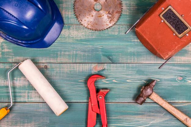 Wałek, młotek, kask, czerwony regulowany klucz do rur, piła tarczowa i maska spawalnicza na ładnym zielonym tle drewna