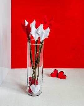 Walentynka dnia gałązki strzała i serca na czerwonym drewnianym tle i szklanej wazie.
