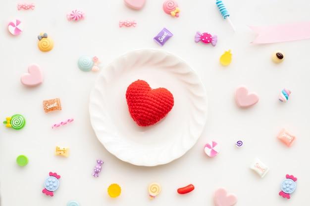 Walentynka dnia tło z czerwonym kierowym kształtem na bielu talerzu