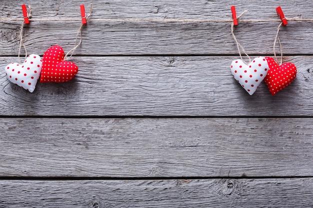 Walentynka z samodzielnie uszytą poduszką, serduszka, obramowane na czerwonych spinaczach do bielizny w rustykalnych szarych deskach