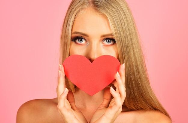 Walentynki. atrakcyjna kobieta z czerwonym sercem. zmysłowa dziewczyna zakrywa usta sercem.