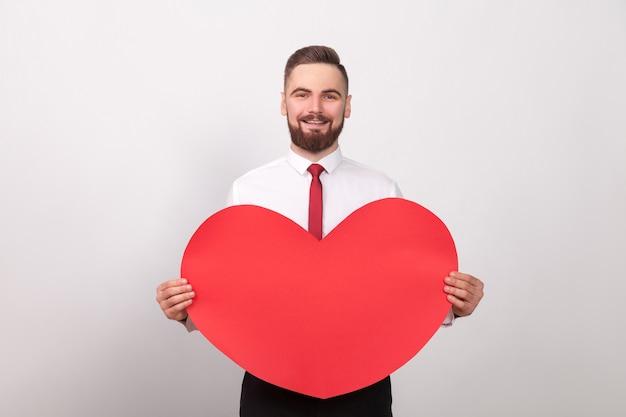 Walentynki. biznesmen energii ząb uśmiechnięty, trzymając duże czerwone serce. wewnątrz, studio strzał, na białym tle na szarym tle