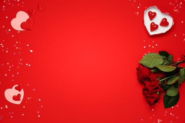 Walentynki. bukiet róż, kształt serca, cukierki czekoladowe na czerwonym tle