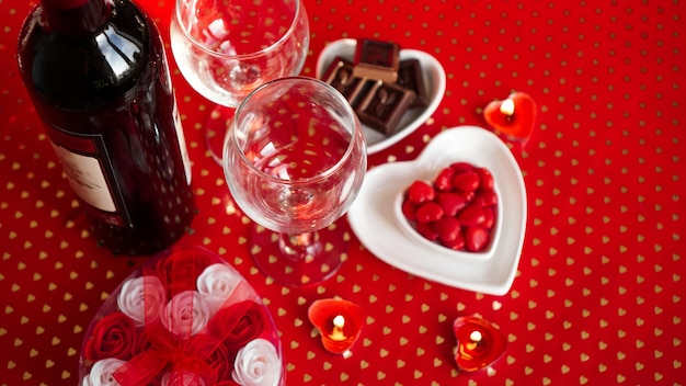 Walentynki. butelka winorośli, okulary, czerwone róże, świece - czerwone tło. koncepcja obiadu miłości