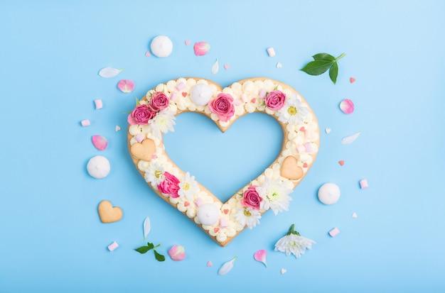 Walentynki ciasto w kształcie serca z kwiatami jako dekoracja.