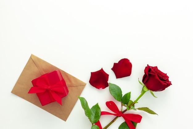 Walentynki. czerwona róża ze wstążką, listem miłosnym i czerwonym pudełkiem.