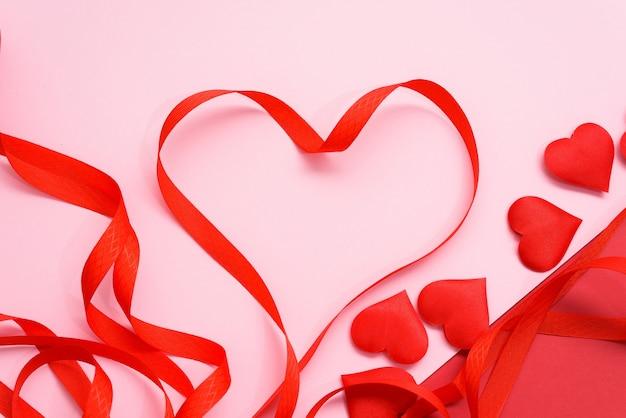 Walentynki czerwona wstążka zakrzywia się w kształcie serca na różowym tle. świąteczne tło na ślub i kartki z życzeniami, makieta, miejsce.