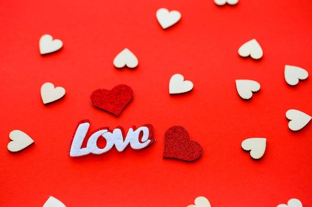 Walentynki czerwone tło z drewnianymi sercami i słowem miłość. miejsce na napisy, reklamę