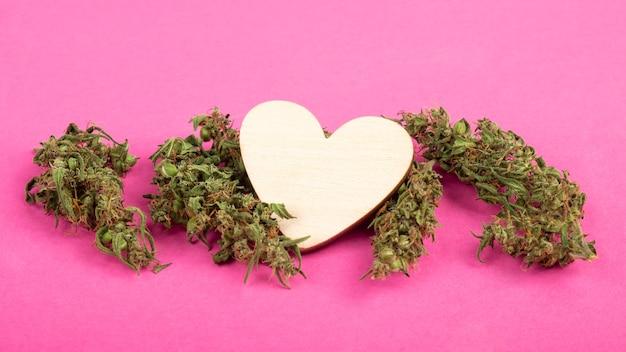 Walentynki drewniane serce i suche pąki konopi symbol miłości na różowym tle