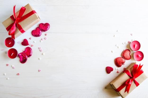 Walentynki drewniane tła z czerwonym sercem, prezenty i świece. prezenty na walentynki. białe drewniane tła