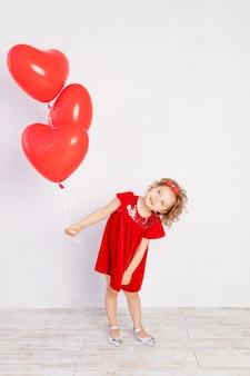Walentynki dzieci. mała dziewczynka w czerwonej sukience trzymając balony w kształcie serca