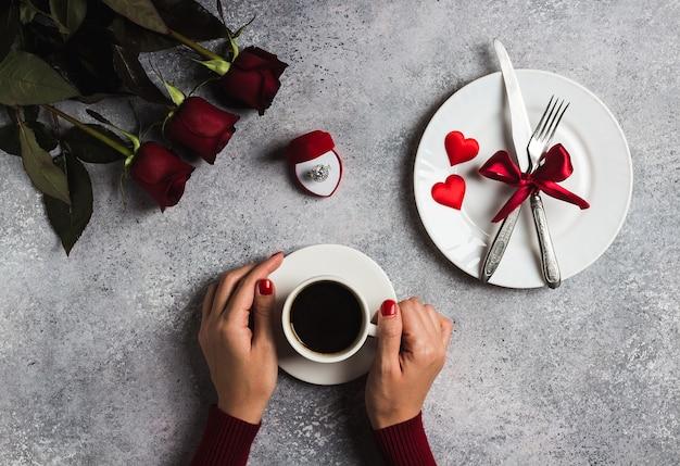 Walentynki-dzień romantyczny stół ustawienie kobieta ręka trzyma filiżankę kawy