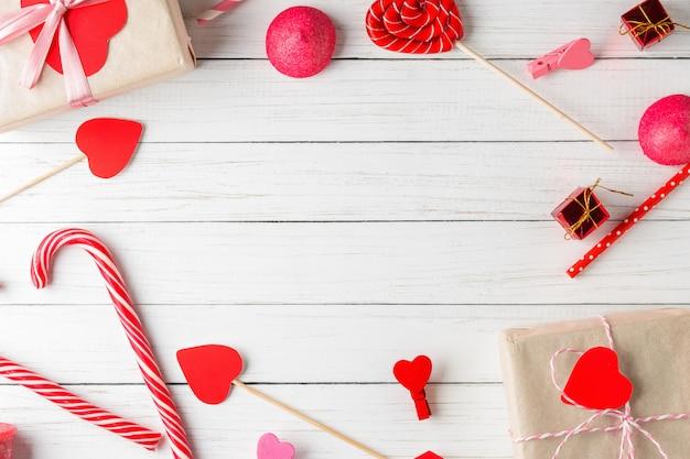 Walentynki-dzień tło. rama czerwoni serca, prezenta pudełko z faborkiem i cukierków cukierki na białym drewnianym tle, odgórny widok