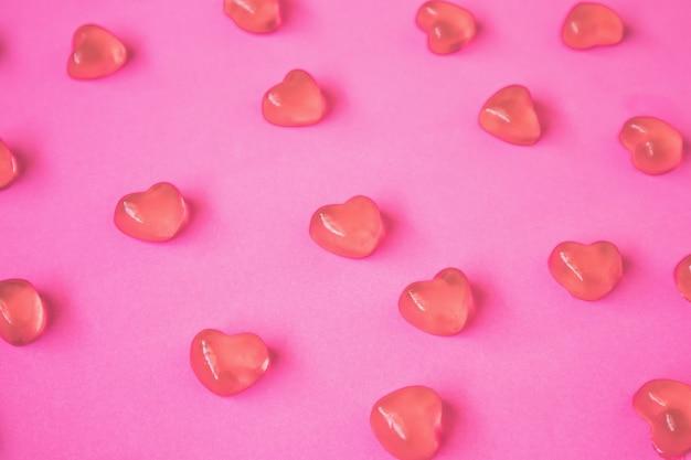 Walentynki-dzień tło z cukierkami w kształcie serca na różowym stole