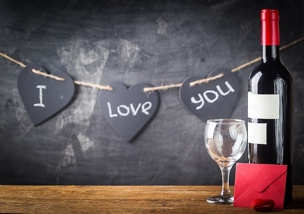 Walentynki-dzień tło z czerwonego wina, kieliszek do wina i karty na błyszczącym tle