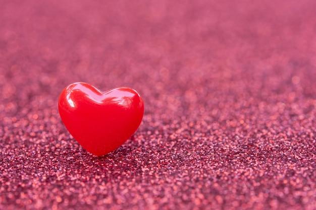 Walentynki-dzień tło z czerwonym sercem kształtuje na abstrakcyjnym tle jasny różowy brokat, miejsce kopiowania