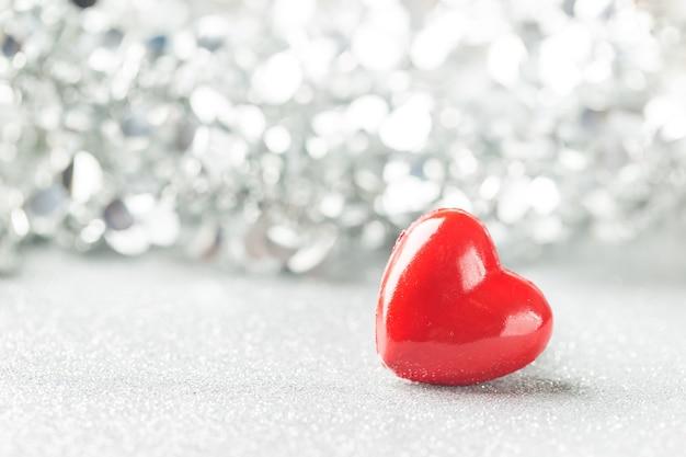 Walentynki-dzień tło z czerwonym sercem na srebrnym tle