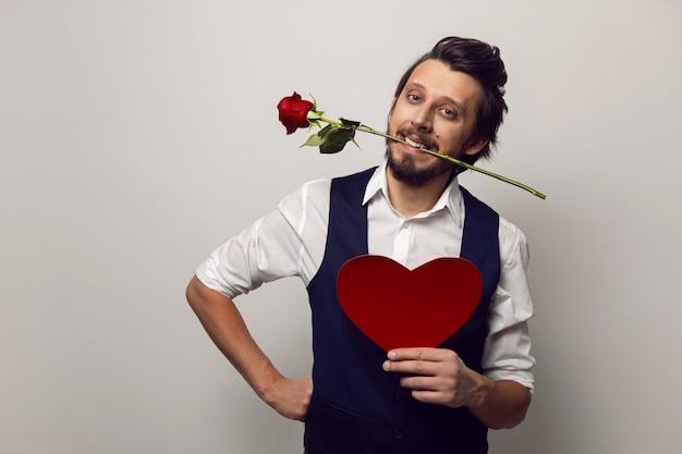 Walentynki elegancki mężczyzna w okularach i brodzie trzyma w ustach czerwone serce i czerwoną różę