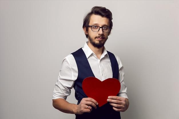 Walentynki elegancki mężczyzna w okularach i brodzie, trzymając czerwone serce na białej ścianie