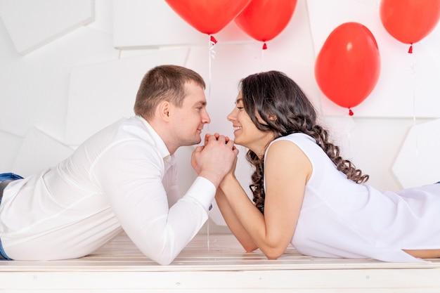 Walentynki, facet z piękną dziewczyną patrzą na siebie z czułym spojrzeniem trzymając się za ręce