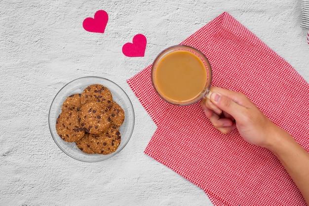 Walentynki. filiżanka kawy i ciasteczka na talerzu na stole, widok z góry