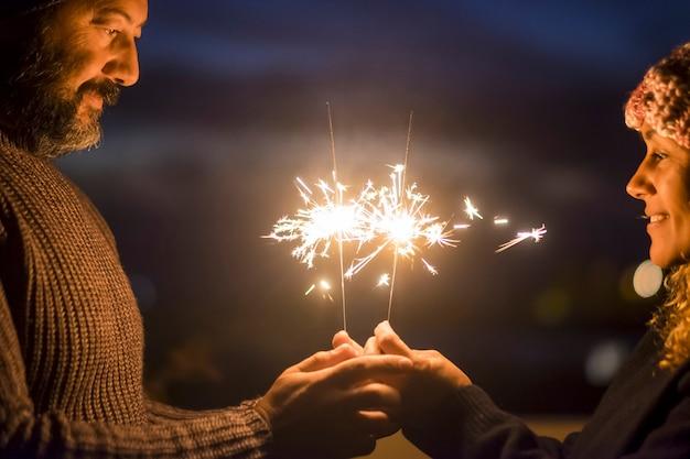 Walentynki i koncepcja miłości celebracja dla kaukaskiego wieku średniego piękna para ciesząca się razem stylem życia i życiem razem z zimnymi ogniami w nocy - szczęśliwi ludzie