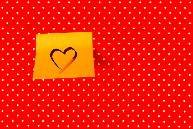 Walentynki i koncepcja miłości. kształt serca napisane na karteczkę na tle czerwonej kropki. białe kropki na czerwonym tle.