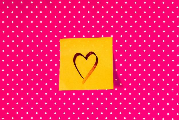 Walentynki i koncepcja miłości. kształt serca napisane na karteczkę na tle czerwonej kropki. białe kropki na różowym tle.