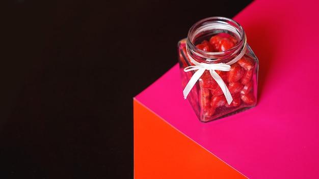 Walentynki i koncepcja miłości. serca w słoiku z czerwonym i czarnym tłem