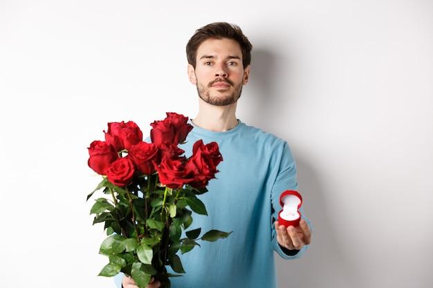 Walentynki i związek. romantyczny chłopak mężczyzna trzyma czerwone róże i pokazuje pierścionek zaręczynowy, składając propozycję w dniu lons, stojąc na białym