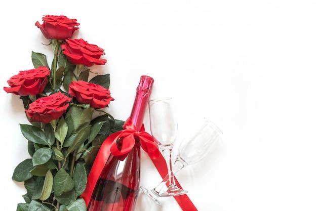 Walentynki karta z czerwonymi różami, szampańska butelka na bielu. widok z góry z płaskim leżał.