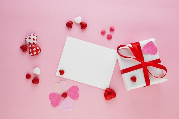 Walentynki kartka z życzeniami z cukierkowymi sercami i prezentem z czerwoną wstążką na różowym stole. widok z góry z miejscem na pozdrowienia.