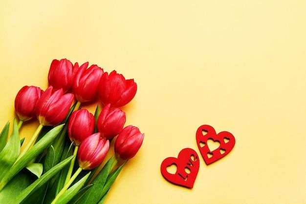 Walentynki kartkę z życzeniami. bukiet czerwonych tulipanów i czerwonych serc na żółto. skopiuj miejsce, leżał płasko