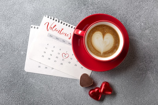 Walentynki kartkę z życzeniami. czerwona filiżanka i cukierki nad kalendarzem lutego. widok z góry