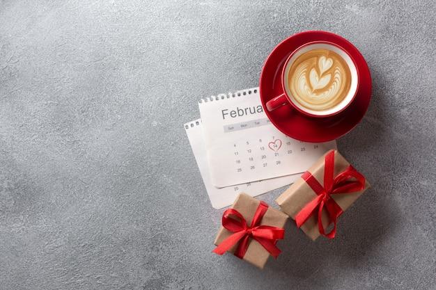 Walentynki kartkę z życzeniami. czerwona filiżanka i prezenta pudełko nad luty kalendarzem. widok z góry